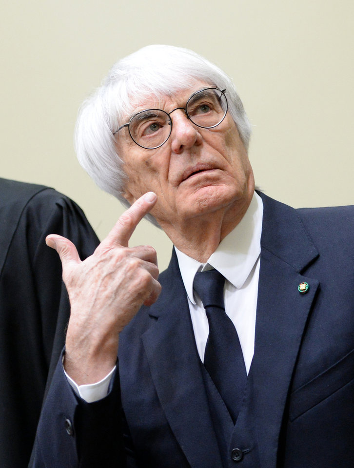 Photo - Formula One boss Bernie Ecclestone points with his finger as he arrives in the regional court in in Munich, Germany, Thursday, April 24, 2014. Ecclestone is charged with bribery and incitement to breach of trust
