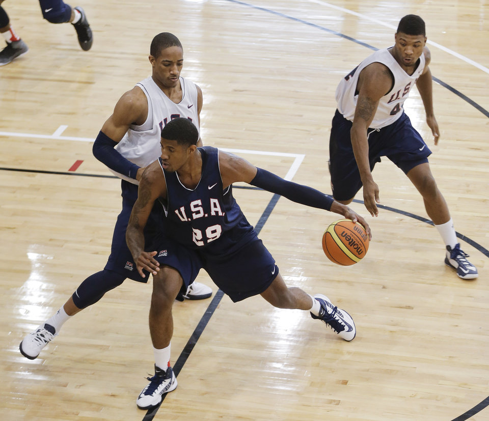 Photo - Indiana Pacers' Paul George (29) drives against Toronto Raptors' DeMar DeRozan, left, and Oklahoma State's Marcus Smart during a USA Basketball minicamp scrimmage, Tuesday, July 23, 2013, in Las Vegas. Twenty-eight of the best young players in the country are in Las Vegas for four days of workouts that essentially mark the kickoff of 2016 Olympic preparations. (AP Photo/Julie Jacobson)  ORG XMIT: NVJJ112