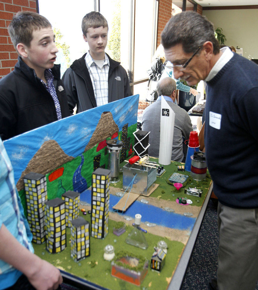 "Sequoyah Middle School students Cooper Coil (left) and Brendan Bussell explain the workings of their city ""Crystal City"" to judge Jim Crimando, during the Future City competition at Oklahoma Christian University in Oklahoma City, OK, Saturday, Jan. 21, 2012. By Paul Hellstern, The Oklahoman"