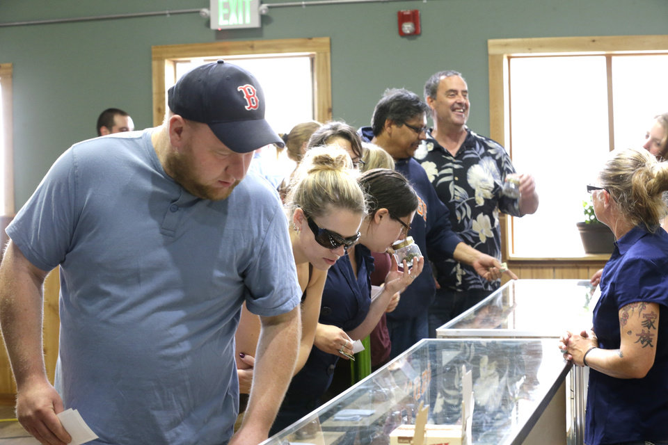 Photo - Customers look at a glass case containing pipes and information on recreational marijuana at Top Shelf Cannabis, Tuesday, July 8, 2014, in Bellingham, Wash., on the first day of legal sales in the state.  (AP Photo/Ted S. Warren)