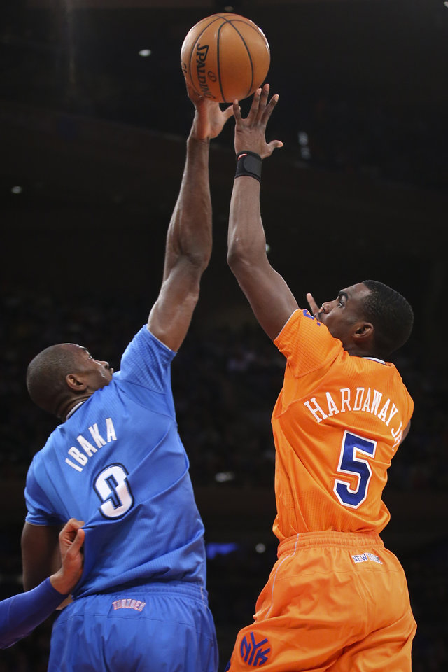 Photo - Oklahoma City Thunder power forward Serge Ibaka (9) blocks a shot from New York Knicks shooting guard Tim Hardaway Jr. (5) during the first half of their NBA basketball game at Madison Square Garden, Wednesday, Dec. 25, 2013, in New York. (AP Photo/John Minchillo)