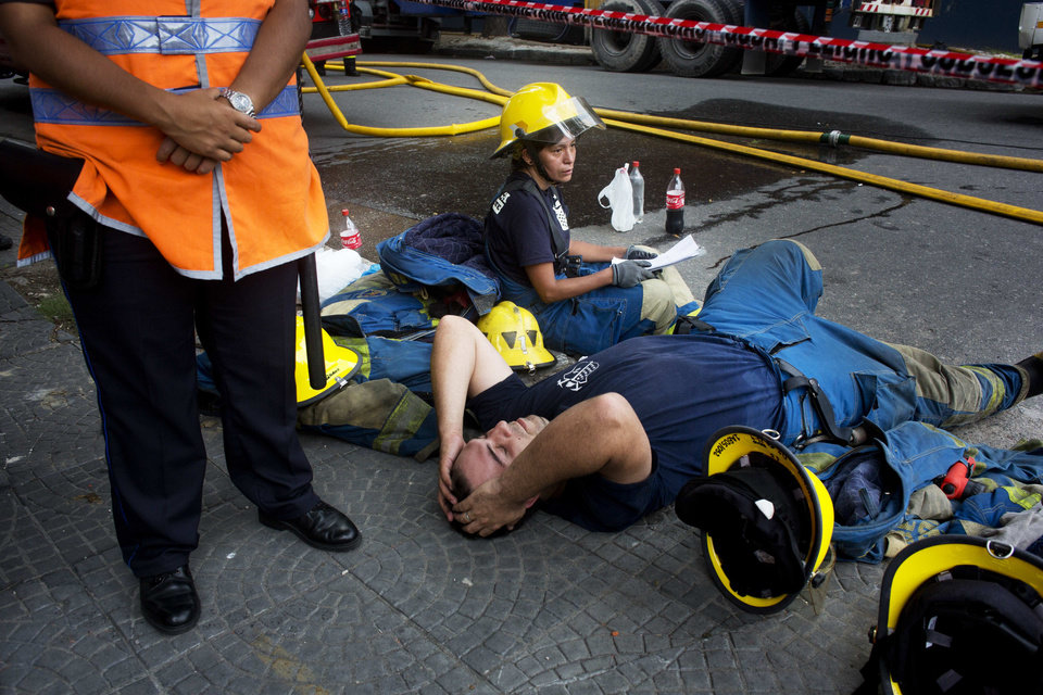 Photo - Firefighters rest after working to extinguish a fire at the Iron Mountain warehouse in Buenos Aires, Argentina, Wednesday, Feb. 5, 2014. Nine first-responders were killed in the fire that destroyed an archive of bank documents, according to authorities. (AP Photo/Rodrigo Abd)