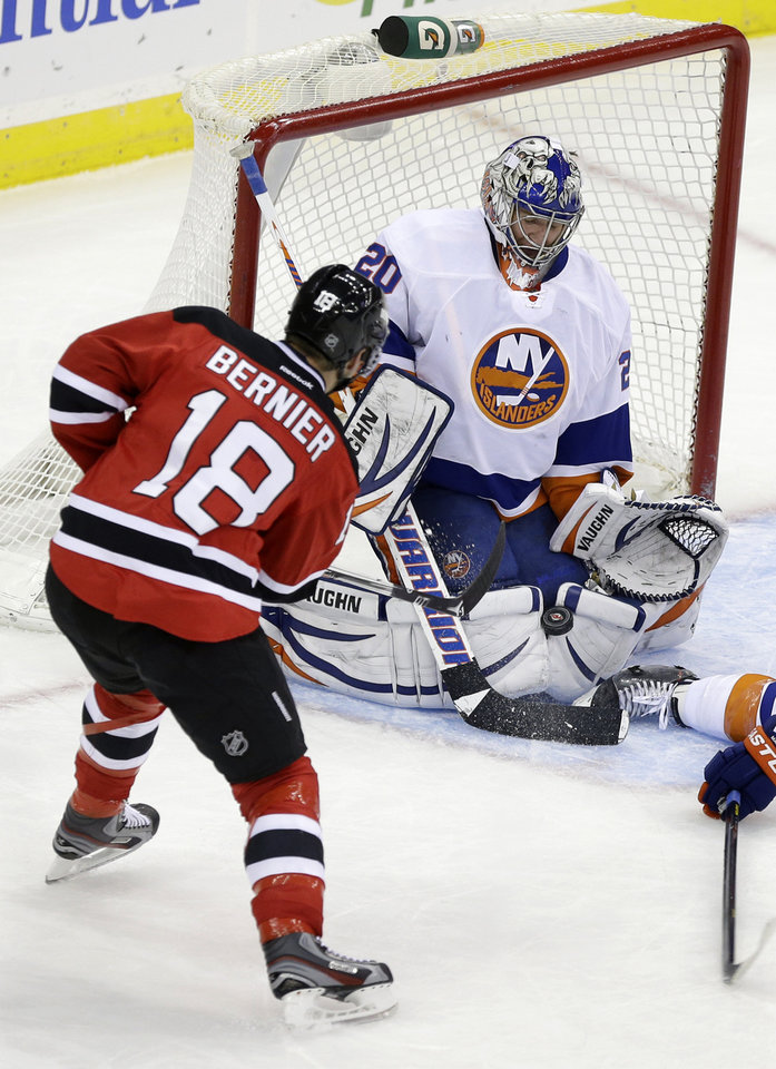 New York Islanders goalie Evgeni Nabokov (20) of Kazakhstan makes a save off his pads on a shot by New Jersey Devils\' Steve Bernier (18) during the second period of an NHL hockey game Monday, April 1, 2013, in Newark, N.J. (AP Photo/Mel Evans)