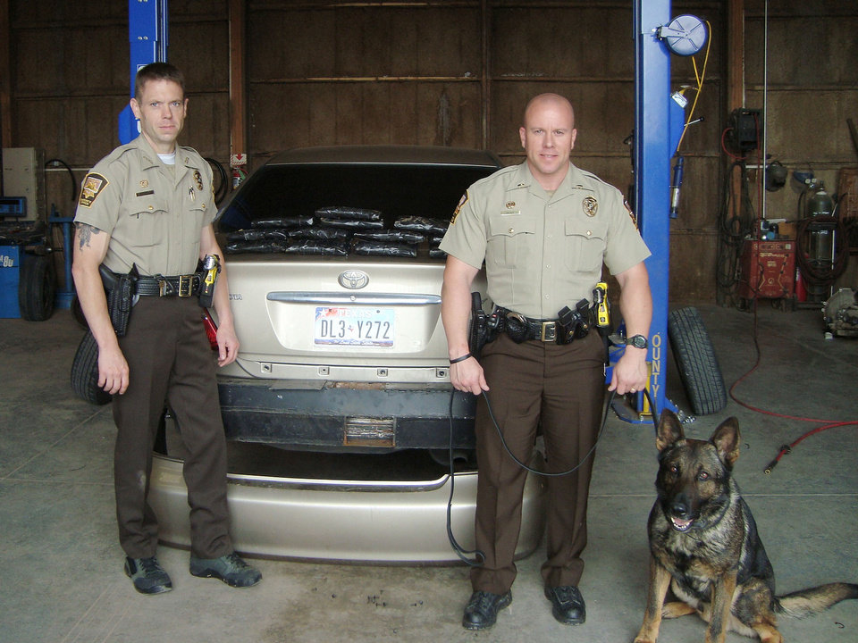 Photo - Canadian County sheriff's deputies Cody Palmer and Lt. Jason Glass and drug dog Gunner stand with the car involved in a cocaine bust along Interstate 40. Photo PROVIDED