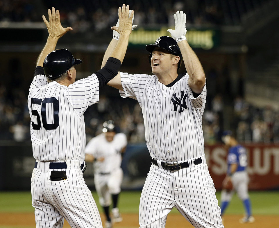 Photo - Newly aquired New York Yankees Chase Headley, right, celebrates with New York Yankees first base coach Mick Kelleher (50) after hitting a game-winning, 14th-inning, walk-off, RBI single in the Yankees 2-1 victory over the Texas Rangers in a baseball game at Yankee Stadium in New York, Wednesday, July 23, 2014. (AP Photo)