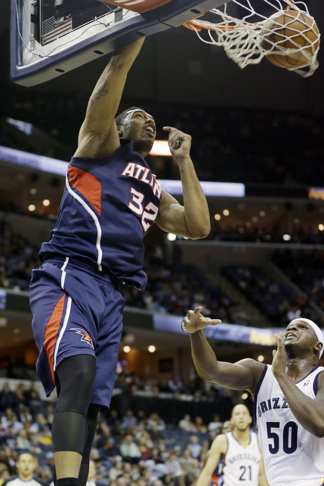 Photo - Atlanta Hawks' Mike Scott (32) dunks the ball over Memphis Grizzlies' Zach Randolph (50) in the first half of an NBA basketball game in Memphis, Tenn., Sunday, Jan. 12, 2014. (AP Photo/Danny Johnston)