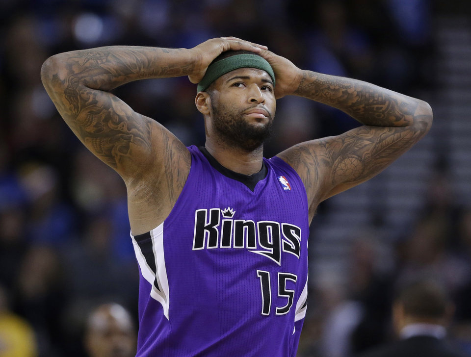 Photo - Sacramento Kings center DeMarcus Cousins (15) walks to the bench after picking up two early fouls against the Golden State Warriors during the first half of an NBA basketball game on Friday, April 4, 2014, in Oakland, Calif. (AP Photo/Marcio Jose Sanchez)