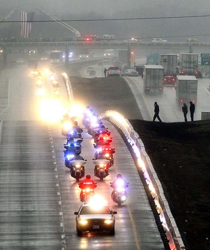 Photo - Traffic along Interstate 35 pulls over and stands in the median, to watch the long funeral procession for slain former Navy SEAL sniper Chris Kyle, as it travels south to his final resting place at the Texas State Cemetery in Austin, Texas, Tuesday, Feb. 12, 2013. Some 7,000 people attended a two-hour memorial service for Kyle at Cowboys Stadium in Arlington on Monday. Kyle and his friend Chad Littlefield were shot and killed Feb 2. at a North Texas gun range. (AP Photo/The Dallas Morning News, Tom Fox)  MANDATORY CREDIT; MAGS OUT; TV OUT; INTERNET OUT; AP MEMBERS ONLY