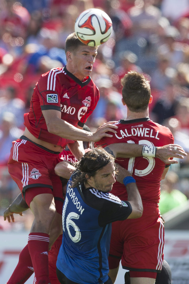 Photo - Toronto FC's Nick Hagglund, left, competes for a header with San Jose Earthquakes' Alan Gordon, center, and Toronto's Steven Caldwell during first half MLS action in Toronto on Saturday June 7, 2014.  (AP Photo/The Canadian Press, Chris Young)