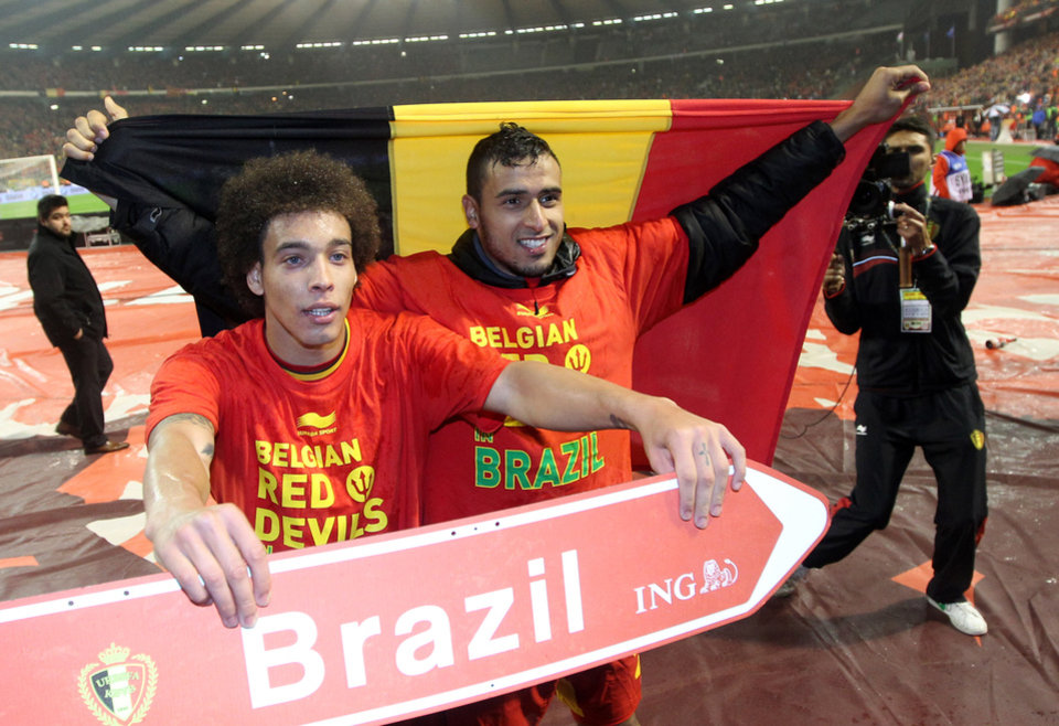 Photo - Belgium's Axel Witsel, left, and Nacer Chadli celebrate after they qualified for the World Cup at the end of the Group A qualifying soccer match against Wales at the King Baudouin stadium in Brussels, Tuesday, Oct. 15, 2013. (AP Photo/Yves Logghe)