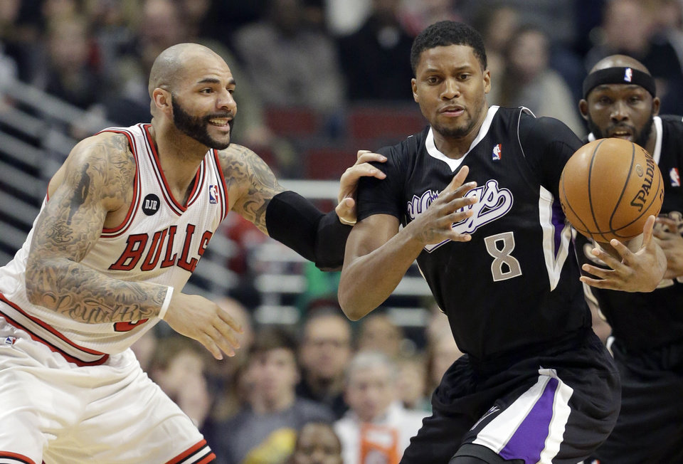 Photo - Sacramento Kings forward Rudy Gay (8), right, controls the ball against Chicago Bulls forward Carlos Boozer during the first half of an NBA basketball game in Chicago on Saturday, March 15, 2014. (AP Photo/Nam Y. Huh)