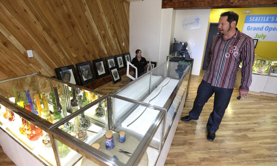 James Lathrop, right, the owner of the recreational marijuana store Cannabis City, checks out display case with glass bongs on display and an empty area awaiting actual marijuana, Monday, July 7, 2014, in Seattle. The store will be the first and only store in Seattle to initially sell recreational marijuana when legal sales begin on Tuesday, July 8, 2014. (AP Photo/Ted S. Warren)