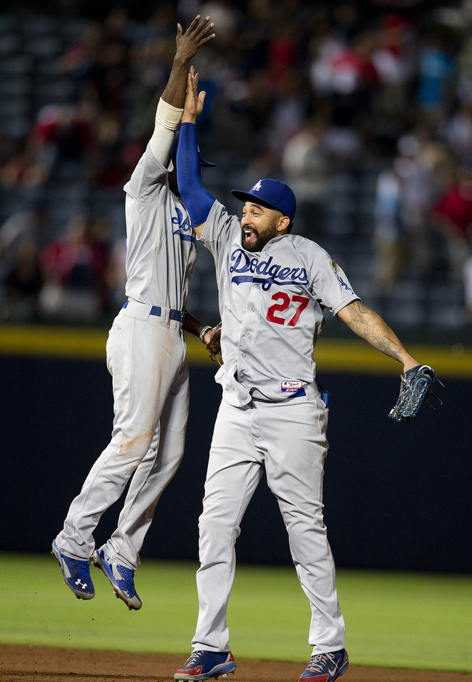 Photo - Los Angeles Dodgers left fielder Matt Kemp (27) and Los Angeles Dodgers second baseman Dee Gordon celebrate after deterring the Atlanta Braves 6-2 in a baseball game  Monday, Aug. 11, 2014 in Atlanta.  (AP Photo/John Bazemore)