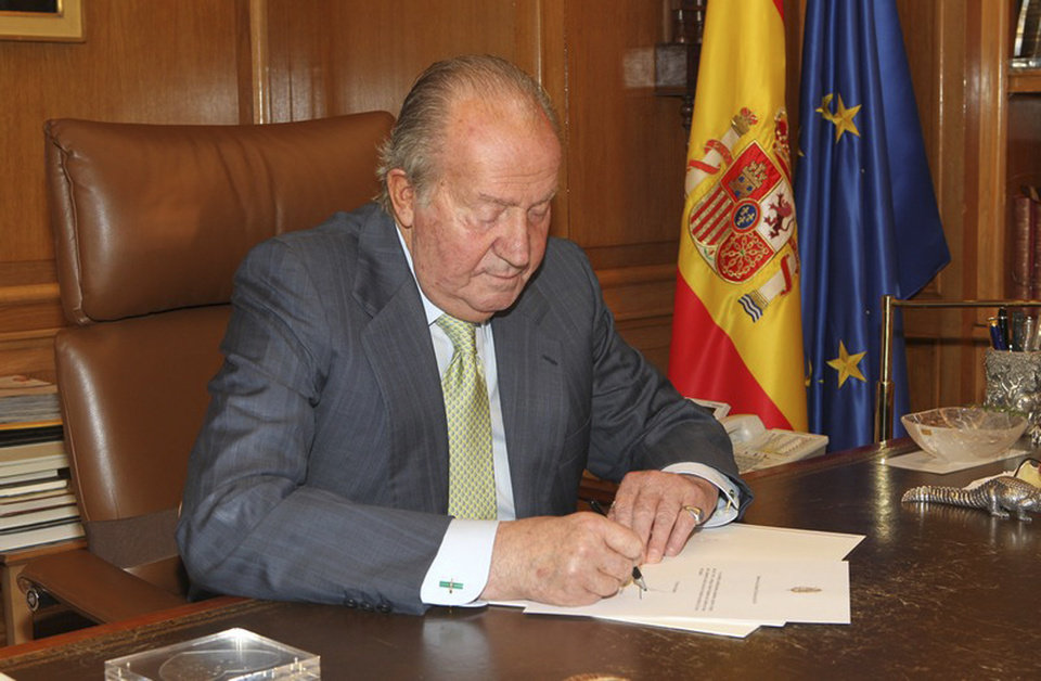 Photo - In this photo released by the Royal Palace on Monday, June 2,  2014,  Spain's King Juan Carlos signs a document in the Zarzuela Palace opening the way for his abdication. Spain's King Juan Carlos plans to abdicate and pave the way for his son, Crown Prince Felipe, to take over, Spanish Prime Minister Mariano Rajoy told the country Monday in an announcement broadcast nationwide. The 76-year-old Juan Carlos oversaw his country's transition from dictatorship to democracy but has had repeated health problems in recent years. (AP Photo/Spanish Royal Palace)