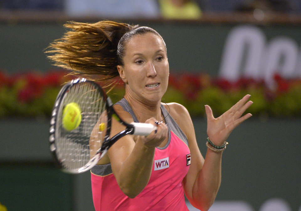 Photo - Jelena Jankovic, of Serbia, returns a shot to Agnieszka Radwanska, of Poland, during their match at the BNP Paribas Open tennis tournament on Wednesday, March 12, 2014, in Indian Wells, Calif. (AP Photo/Mark J. Terrill)