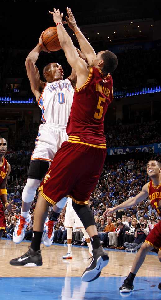 Photo - Oklahoma City's Russell Westbrook (0) tries to get a shot off beside Cleveland's Ryan Hollins (5) during the NBA basketball game between the Oklahoma City Thunder and the Cleveland Cavaliers at Chesapeake Energy Arena in Oklahoma City, Friday, March 9, 2012. Photo by Bryan Terry, The Oklahoman