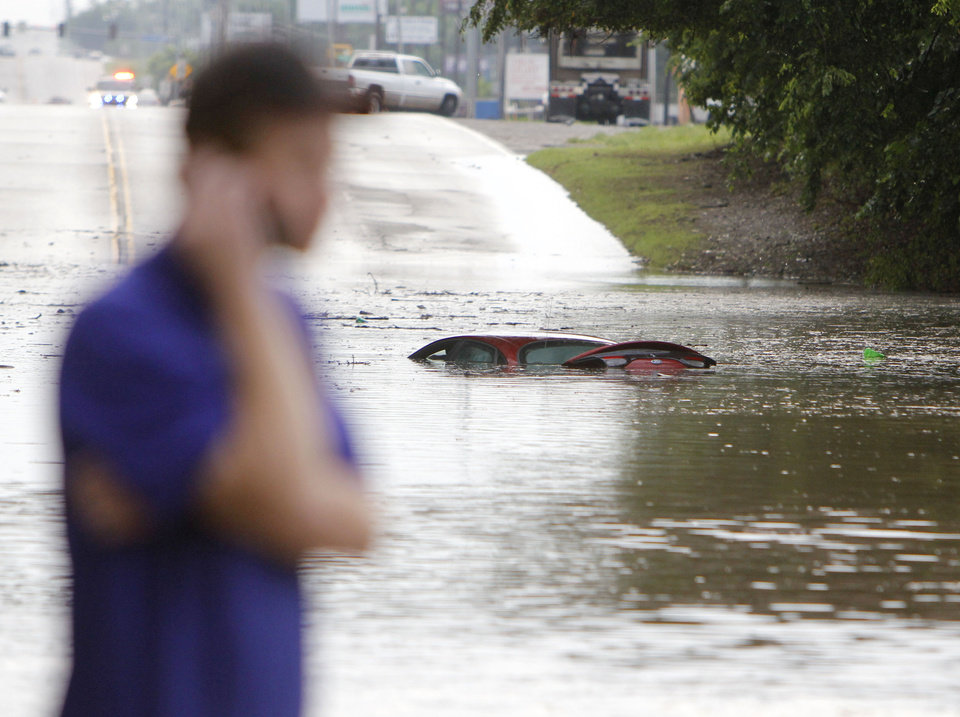 A motorist calls for assistance after losing his car in floodwaters between Sooner Rd. and Air Depot Blvd. on NE 23rd St. in Midwest City, OK, Saturday, June 1, 2013, after up to eight inches of rain fell during the previous 24 hours. Photo by Paul Hellstern, The Oklahoman
