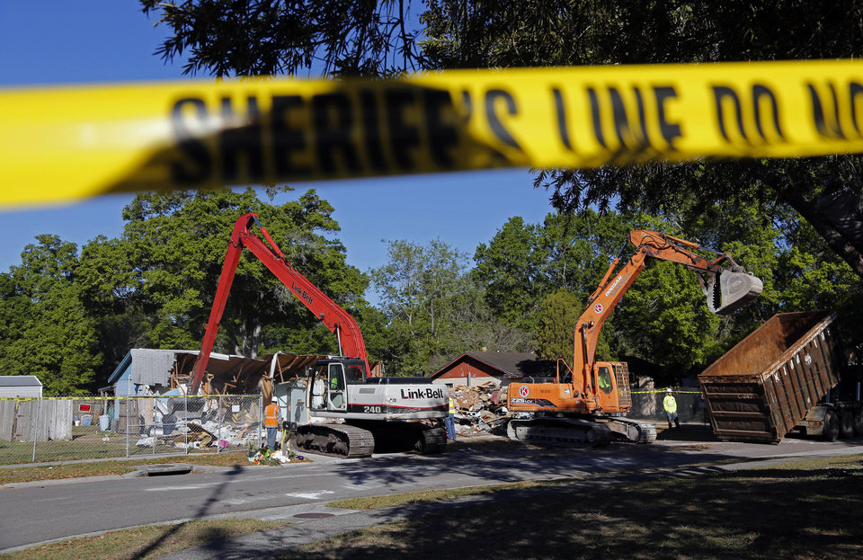 Photo - Demolition experts watch as the home of Jeff Bush  is destroyed Monday, March 4, 2013 in Seffner, Fla.  A sinkhole opened up underneath the house late Thursday, Feb. 28, 2013, swallowing Bush, 37.  The 20-foot-wide opening of the sinkhole was almost covered by the house, and rescuers said there were no signs of life since the hole opened Thursday night.  (AP Photo/Scott Iskowitz)