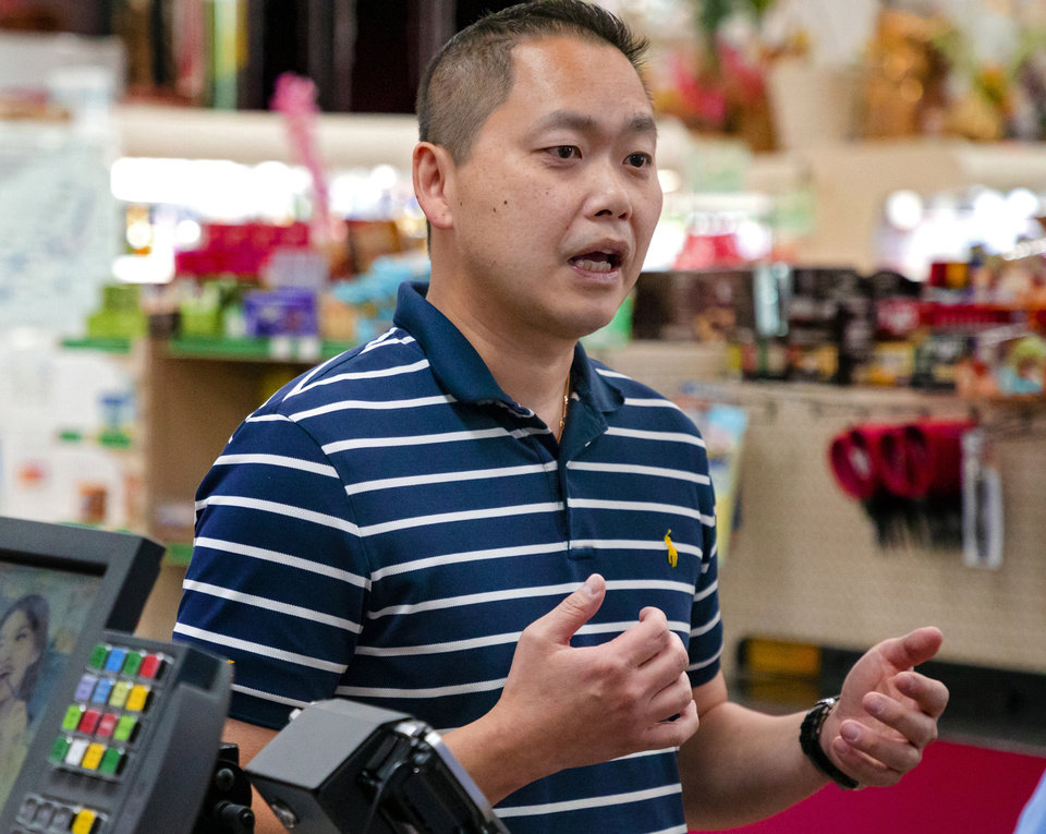Photo -  Super Cao Nguyen's Ba Luong talks about the newly installed plexiglass barriers between customers and cashiers to help prevent the spread of COVID-19. [Chris Landsberger/The Oklahoman]