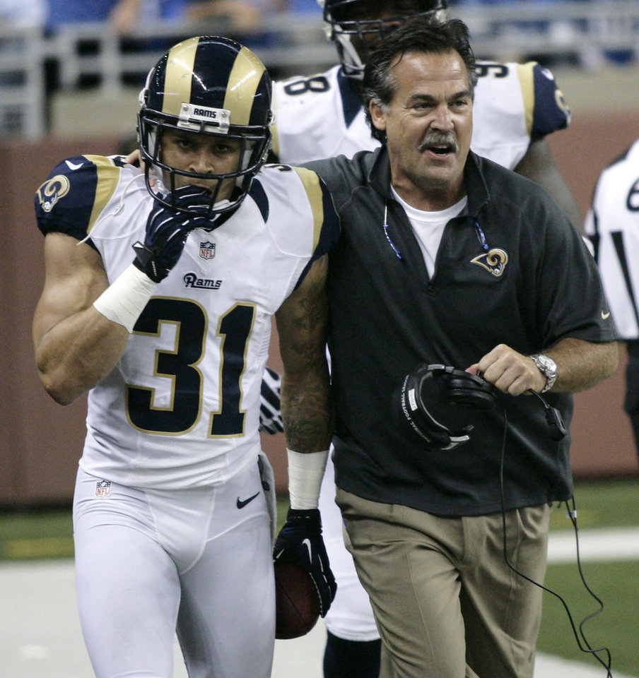 Photo -   St. Louis Rams defensive back Cortland Finnegan (31) celebrates his interception and 31-yard return for a touchdown with coach Jeff Fisher in the second quarter of an NFL football game against the Detroit Lions, Sunday, Sept. 9, 2012, in Detroit. (AP Photo/Duane Burleson)