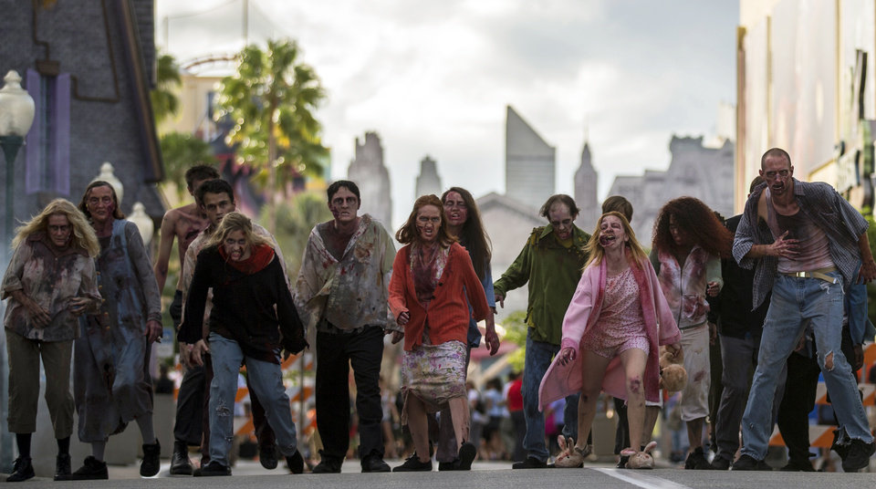 """Photo - This September 2013 image provided by Universal Orlando in Orlando, Fla., shows actors portraying zombies for the theme park's Halloween Horror Nights, which take place on select nights through Nov. 2. The zombies are inspired by AMC's show """"The Walking Dead."""" One of the park's eight haunted houses is also themed on the show. (AP Photo/Universal Orlando) ORG XMIT: NYET308"""