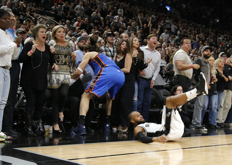 Photo - Oklahoma City's Steven Adams (12) falls into the crowd as San Antonio's Patty Mills (8) watches his shot in the last seconds of Game 2 of the second-round series between the Oklahoma City Thunder and the San Antonio Spurs in the NBA playoffs at the AT&T Center in San Antonio, Monday, May 2, 2016. Oklahoma City won 98-97. Photo by Bryan Terry, The Oklahoman