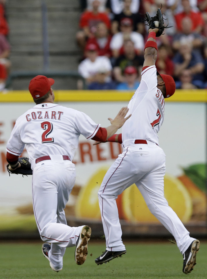 Photo - Cincinnati Reds second baseman Ramon Santiago (7) avoids a collision with shortstop Zack Cozart (2) as he catches a pop fly hit by Arizona Diamondbacks' Martin Prado in the fourth inning of a baseball game, Tuesday, July 29, 2014, in Cincinnati. (AP Photo/Al Behrman)