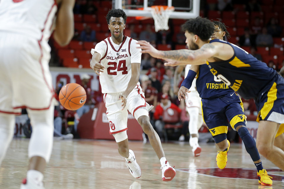 Photo - Oklahoma's Jamal Bieniemy (24) passes the ball during an NCAA college basketball game between the University of Oklahoma (OU) and West Virginia at Lloyd Noble Arena in Norman, Okla.,  Saturday, March 2, 2019. Oklahoma won 92-80. Photo by Bryan Terry, The Oklahoman
