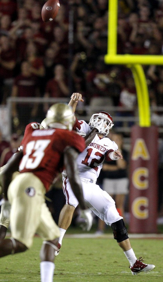 Oklahoma's Landry Jones (12) gets hut as he throws an interception during a college football game between the University of Oklahoma (OU) and Florida State (FSU) at Doak Campbell Stadium in Tallahassee, Fla., Saturday, Sept. 17, 2011. Photo by Bryan Terry, The Oklahoman