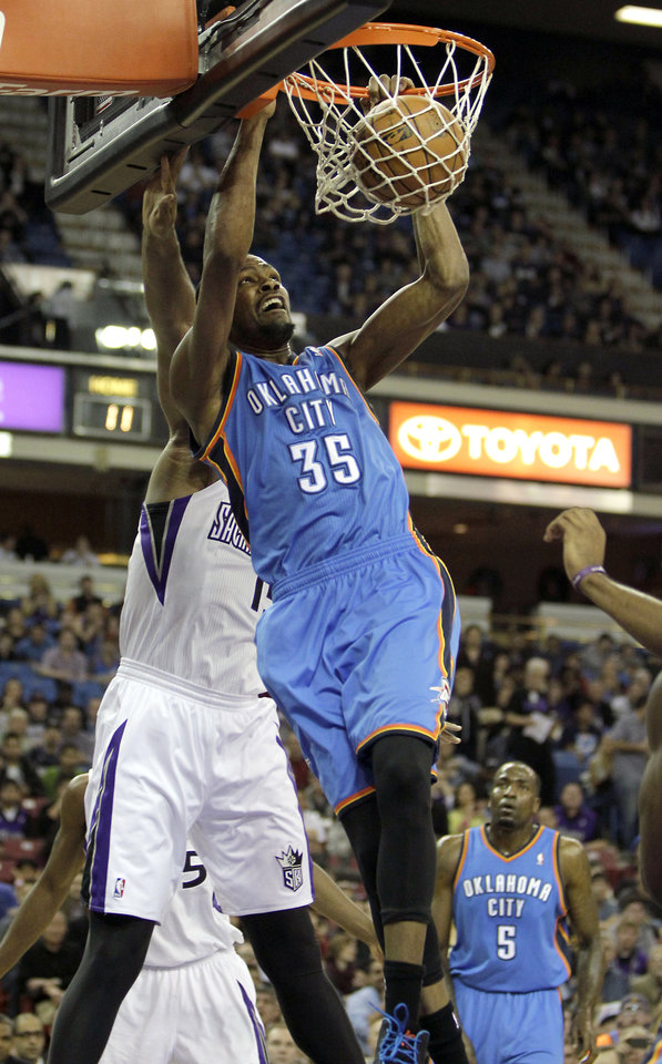 Photo - Oklahoma City Thunder forward Kevin Durant (35) stuffs the ball against Sacramento Kings center DeMarcus Cousins, left, during the first quarter of an NBA basketball game in Sacramento, Calif., Friday, Jan. 25, 2013. (AP Photo/Rich Pedroncelli)