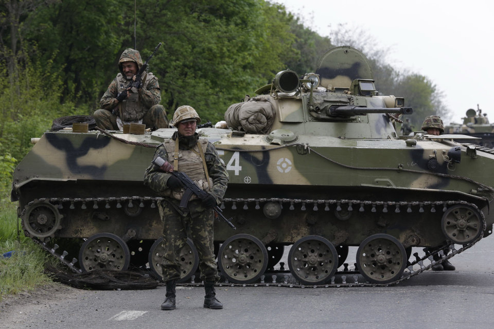 Photo - Ukrainian soldiers stand guard on a road leading to Slovyansk, eastern Ukraine, Friday, May 2, 2014. Ukraine launched what appeared to be its first major assault against pro-Russian forces who have seized government buildings in the country's east, with fighting breaking out Friday in a city that has become the focus of the insurgency. (AP Photo/Max Vetrov)