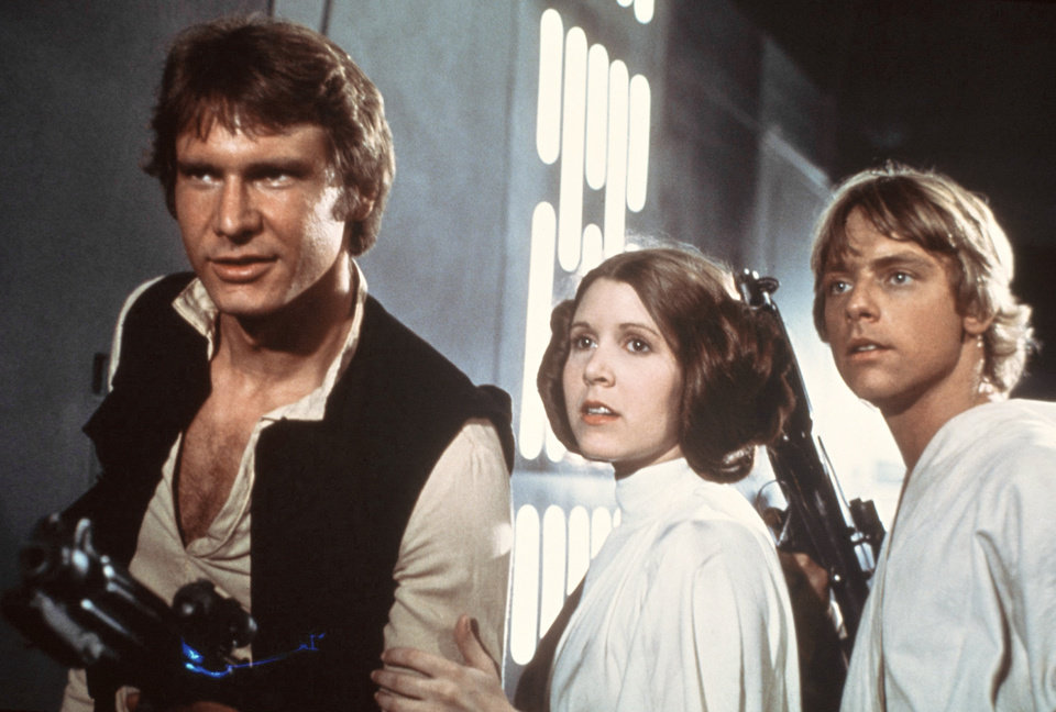 Photo - FILE - This 1977 file image provided by 20th Century-Fox Film Corporation ahows, from left, Harrison Ford, Carrie Fisher, and Mark Hamill in a scene from