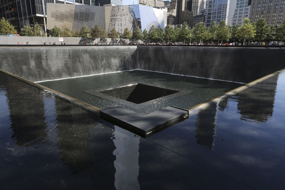 Photo - The National September 11 Museum is seen beyond the North Pool in the Memorial, Friday, Sept. 6, 2013 in New York. Construction is racing ahead inside the museum as the 12th anniversary of the Sept. 11, 2001 attacks draws near. Several more large artifacts have been installed in the cavernous space below the World Trade Center memorial plaza. (AP Photo/Mary Altaffer)