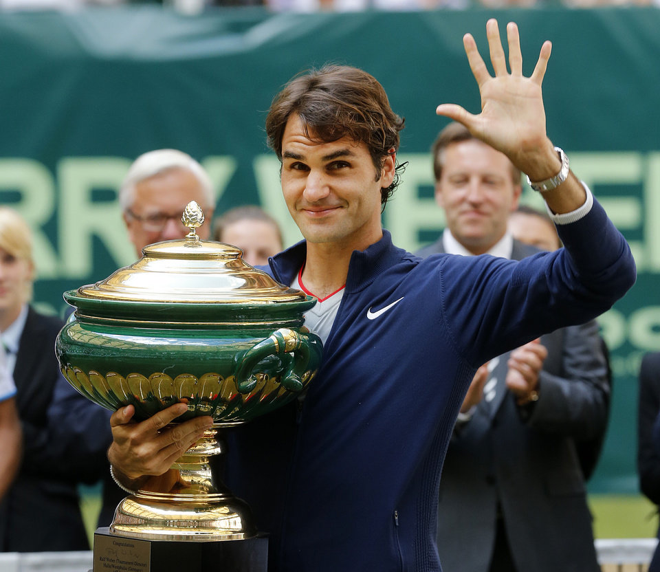 Photo - Switzerland's Roger Federer holds the trophy and waves after winning the final of the Gerry Weber Open tennis tournament in Halle, Germany, Sunday, June 15, 2014. Federer beat Colombia's Alejandro Falla 7-6 and 7-6. (AP Photo/Michael Probst)