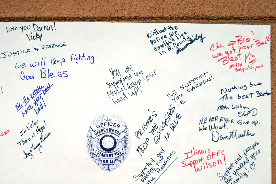 Photo - Well-wishers sign a poster in support of Ferguson police Officer Darren Wilson during a rally for him on Saturday, Aug. 23, 2014, at Barney's Sports Pub along Chippewa Street in St. Louis. Ferguson's streets remained peaceful as tensions between police and protesters continued to subside after nights of violence and unrest that erupted when Wilson, a white police officer, fatally shot Michael Brown, an unarmed black 18-year-old. (AP Photo/St. Louis Post-Dispatch, Huy Mach)  EDWARDSVILLE INTELLIGENCER OUT; THE ALTON TELEGRAPH OUT
