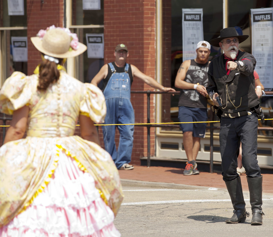 Photo - The Guthrie Gunfighters broke into a gunfight on the streets of downtown Guthrie during the Gentlemen of the Road Stopover Friday, September 6, 2013. Photo by Nathan Poppe, for The Oklahoman