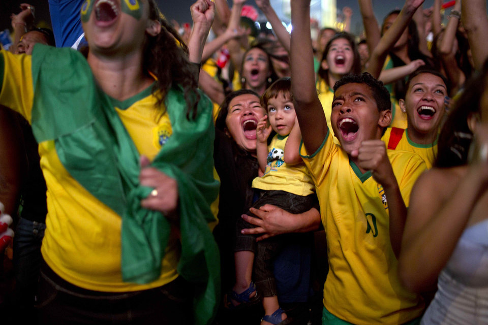Photo - Brazil soccer fans celebrate a goal as they watch a live telecast of the World Cup quarterfinal between Brazil and Colombia inside the FIFA Fan Fest area in Taquatinga, Brazil, Friday, July 4, 2014. Brazil won 2-1. (AP Photo/Rodrigo Abd)