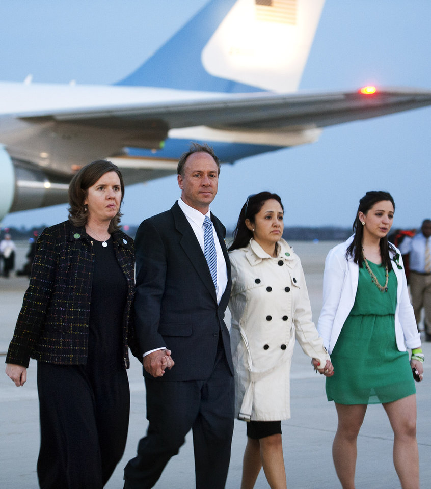Photo - Mark and Jackie Barden, parents of 7 year-old Daniel, left, walk with Nelba Marquez-Greene, mother of 6 year-old Ana, center, and an unidentified woman from Air Force One to waiting White House vans after landing at Andrews Air Force Base, Md., Monday, April 8, 2013 with President Barack Obama and other families who lost relatives in the Sandy Hook Elementary School shooting. Obama was returning from Hartford, Conn., where he spoke at the University of Hartford, near the state capitol where last week the governor signed into law some of the nation's strictest gun control laws. (AP Photo/Cliff Owen)