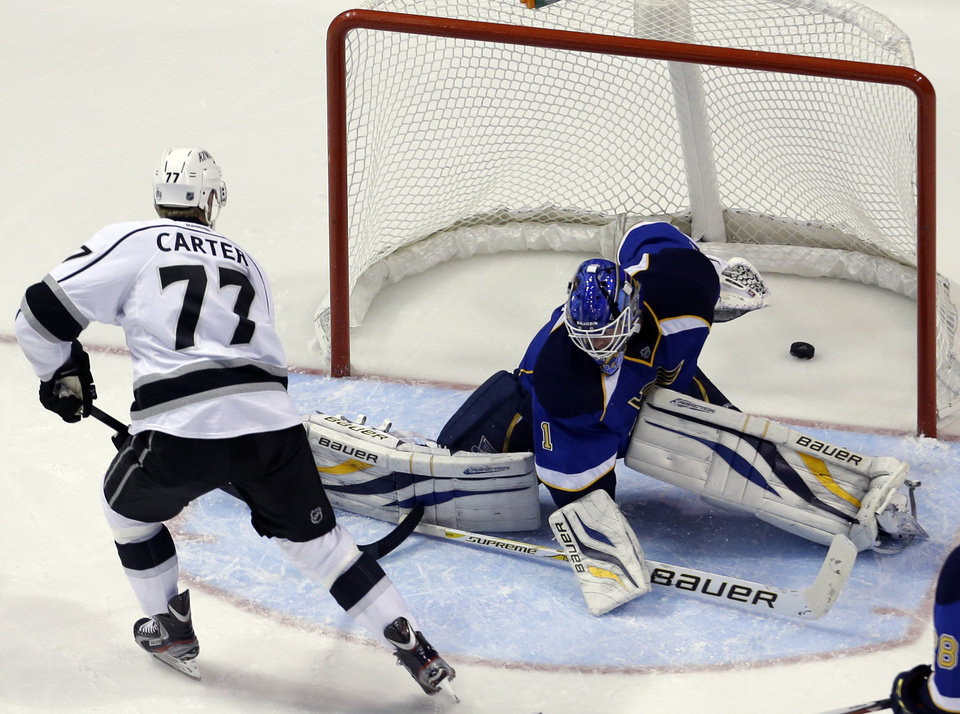 Photo - Los Angeles Kings' Jeff Carter, left, scores his second goal of an NHL hockey game past St. Louis Blues goalie Brian Elliott during the second period, Monday, Feb. 11, 2013, in St. Louis. (AP Photo/Jeff Roberson)