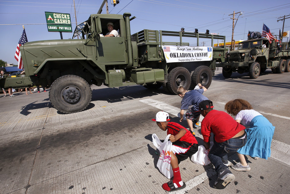 Children, with plastic bags in their hands, chase after pieces of candy thrown by the driver of this military truck during the Armed Forces Day parade in Del City, Saturday morning,  May 11, 2013. Photo  by Jim Beckel, The Oklahoman.