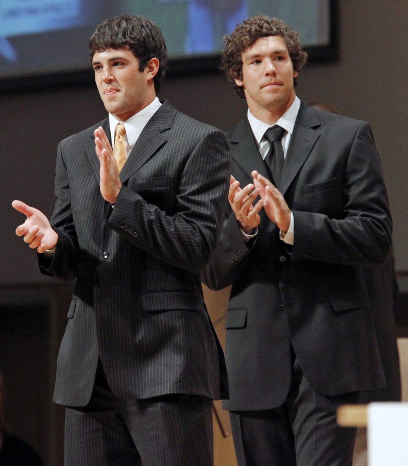 Photo - OKLAHOMA STATE UNIVERSITY / UNIVERSITY OF OKLAHOMA / COLLEGE FOOTBALL PLAYERS / FCA BANQUET: OSU quarterback Zac Robinson, left, and OU quarterback Sam Bradford applaud during the Fellowship of Christian Athletes All-State Banquet at the National Cowboy & Western Heritage Museum in Oklahoma City, Monday, April 27, 2009. Robinson and Bradford were special guests at the event. Photo by Nate Billings, The Oklahoman ORG XMIT: KOD
