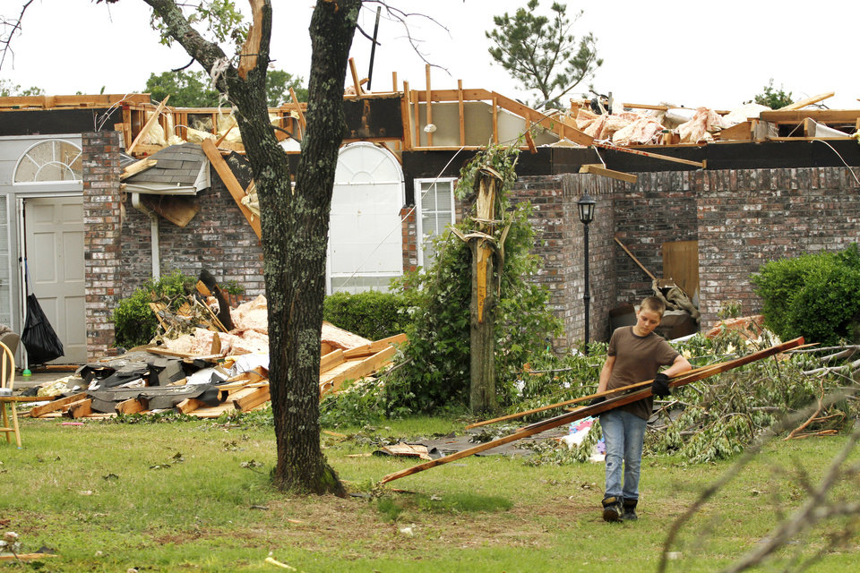 Brighton Godwin carries broken boards to the street in the Dripping Springs Estates Saturday, May 15, 2010. Saturday hundreds of volunteers went into areas that had been affected by last week's tornadoes to help clear debris. Photo by Doug Hoke, The Oklahoman.