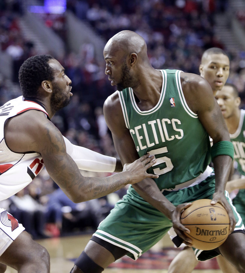 Boston Celtics forward Kevin Garnett, right, looks for an opening against Portland Trail Blazers center J.J. Hickson during the first quarter of an NBA basketball game in Portland, Ore., Sunday, Feb. 24, 2013. (AP Photo/Don Ryan)