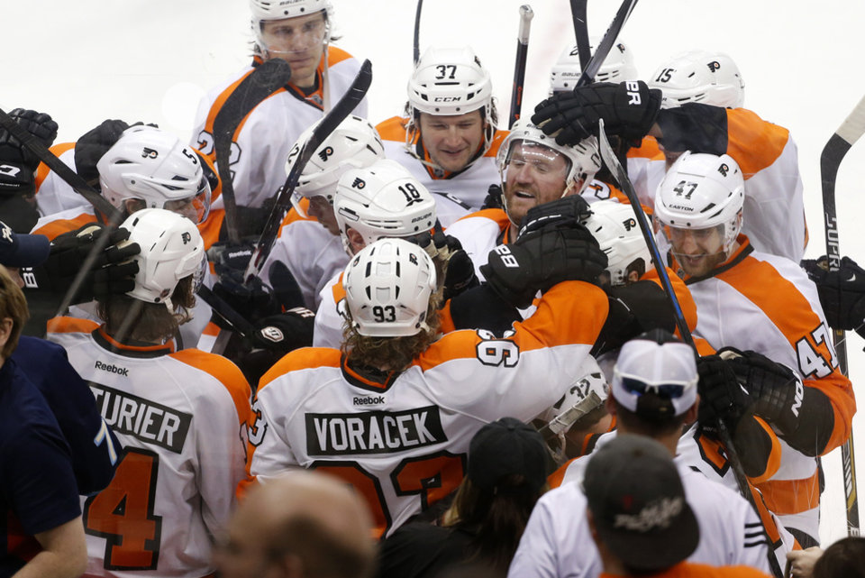 Photo - The Philadelphia Flyers celebrate after Philadelphia Flyers' Mark Streit (32) scored the game winning goal in overtime of an NHL hockey game against the Pittsburgh Penguins in Pittsburgh, Saturday, April 12, 2014. The Flyers won 4-3 in overtime. (AP Photo/Gene J. Puskar)