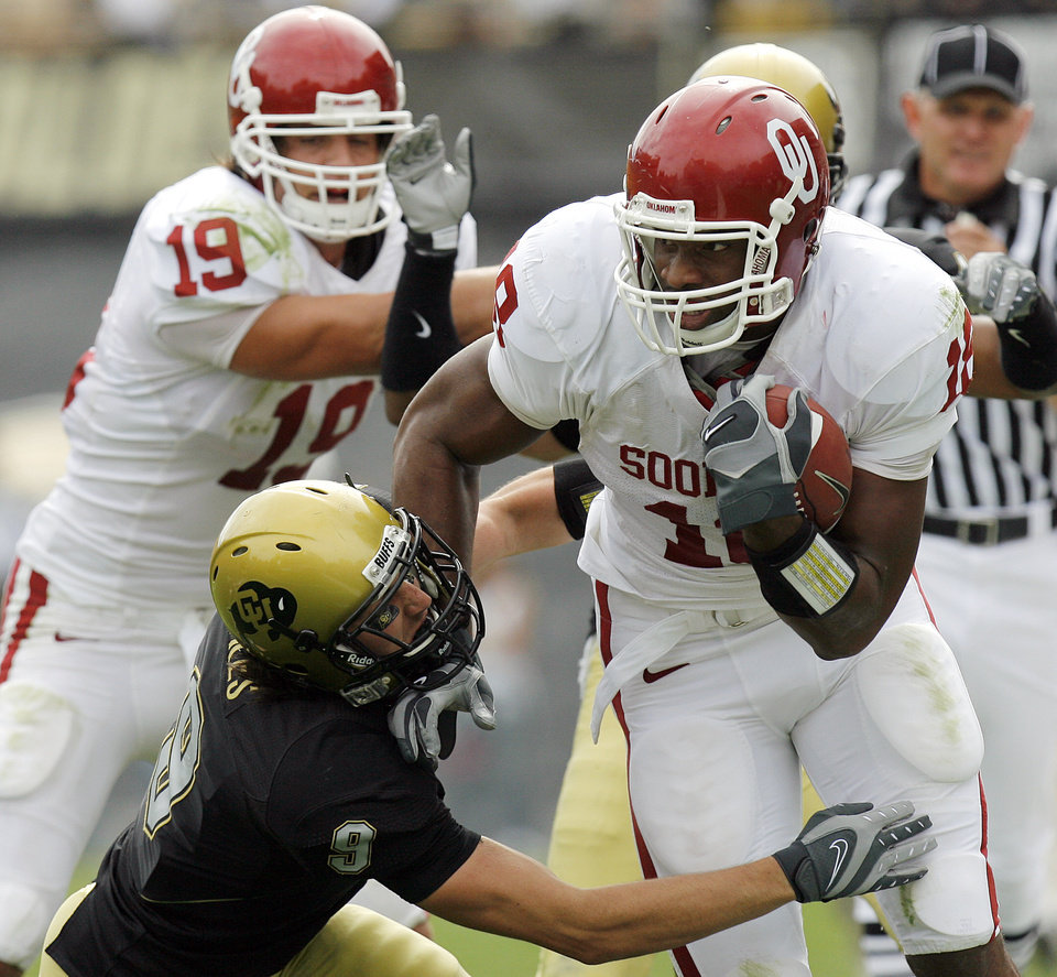 Oklahoma's Jermaine Gresham (18) runs over Colorado's Daniel Dykes (9) as he takes the ball up field during the first half of the college football game between the University of Oklahoma Sooners (OU) and the University of Colorado Buffaloes (CU) at Folsom Field in Boulder, Co., on Saturday, Sept. 28, 2007. 