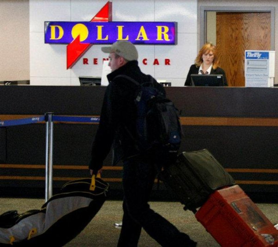 A Dollar Thrifty employee works behind a counter at Tulsa International Airpor while a traveler passes by. CORY YOUNG/Tulsa World