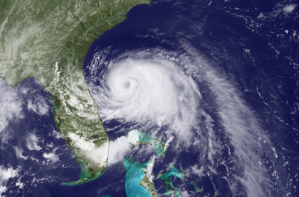Photo - This Wednesday, July 2, 2014, satellite image taken at 3:35 p.m. EDT and released by the National Oceanic and Atmospheric Administration (NOAA), shows Tropical Storm Arthur moving north off the east coast of Florida. The first named storm of the Atlantic hurricane season has strengthened to a hurricane early Thursday, July 3, 2014, and threatened to give North Carolina a glancing blow on Independence Day, prompting the governor to warn vacationers along the coast not to risk their safety by trying to salvage their picnics and barbecues. (AP Photo/NOAA)
