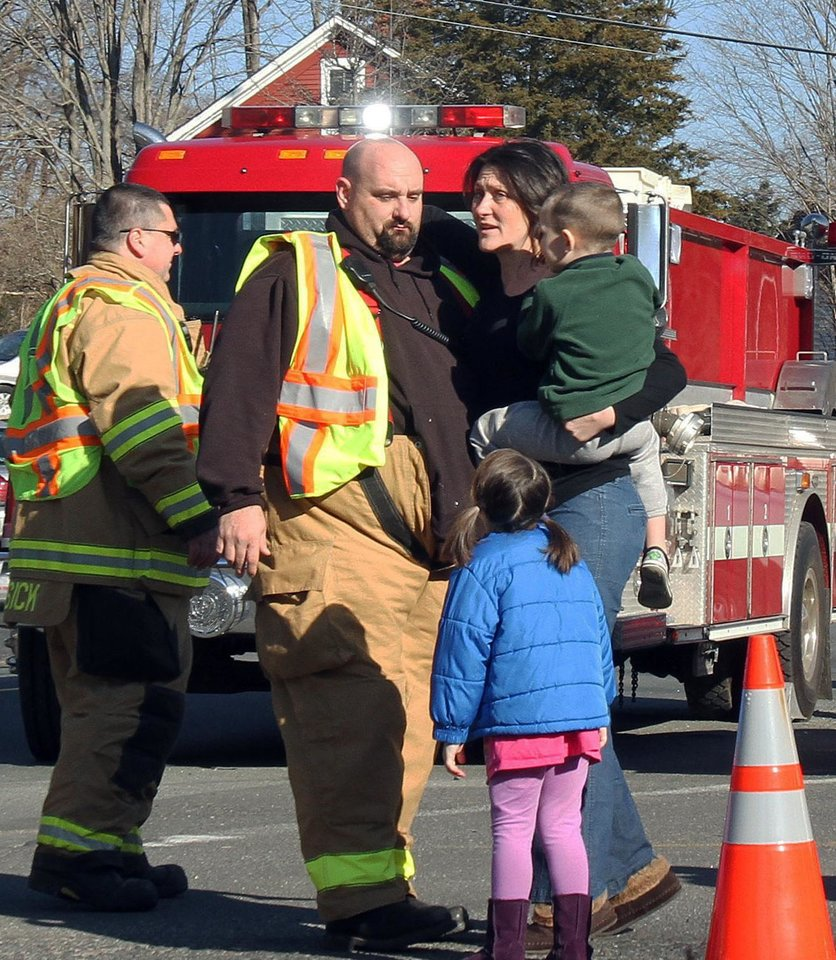 Photo - FILE - In this Dec. 14, 2012 file photo, a woman holding her children embraces a firefighter shortly after Adam Lanza opened fire, killing 26 people, including 20 children. While the people of Newtown do their best to cope with loss and preserve the memories of their loved ones, another class of residents is also finding it difficult to move on: the emergency responders who saw firsthand the terrible aftermath of last week's school shooting. (AP Photo/The Journal News, Frank Becerra Jr., File) NYC OUT, NO SALES, TV OUT, NEWSDAY OUT; MAGS OUT; MANDATORY CREDIT: THE JOURNAL NEWS, FRANK BECERRA JR.