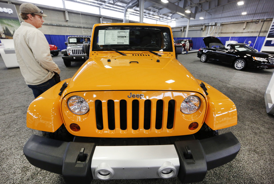 Photo - Jeremy Miller looks at a Jeep Wrangler  at the Oklahoma City International Auto Show, which continues through Sunday at State Fair Park.  Steve Gooch - The Oklahoman