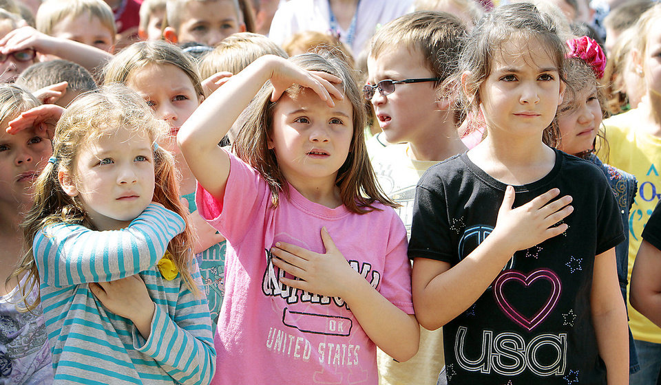 Photo - Cayman Casey, Isabella Tarantelli and Charlie Ziegler salute during the Pledge of Allegiance.